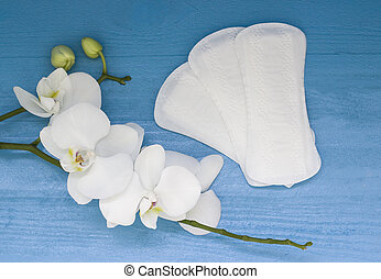 Sanitary pads and lilac orchid on blue wooden background
