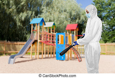 disinfection service and pandemic concept - sanitation worker in protective gear, medical mask, gloves and goggles with pressure washer or sanitizer over children's playground background