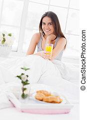 sano, comienzo, de, el, day., alegre, joven, mujer sonriente, sostener un cristal, con, jugo, mientras, el sentarse en cama, con, un, desayuno, colocar, en, bandeja