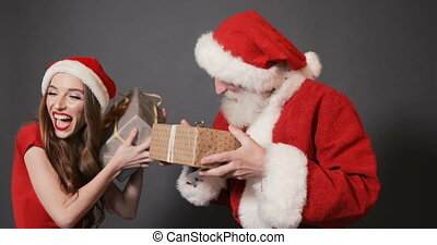 Santa and Helper Give Christmas Gifts - Thrilled santa claus...