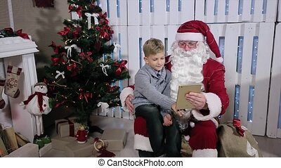 Santa and Little Boy Choose Gifts on Tablet, Sit Near a Christmas Tree with Gifts
