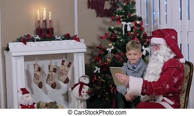Santa and Little Boy Choose Gifts on Tablet, Sit Near a Christmas Tree with Gifts in Room with Fireplace