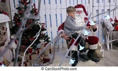 Santa and the Little Boy Choose Gifts on Tablet, Sitting Near the Tree with a Tablet, Shooting Through the Tree, Change Focus