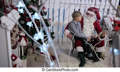 Santa and the Little Boy Sitting Near the Tree with a Tablet, Shooting Through the Tree