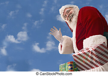 Santa Claus against a baby blue sky - Santa Claus with bag...