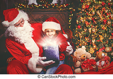 Santa Claus and child girl with bright magical gift in Christmas