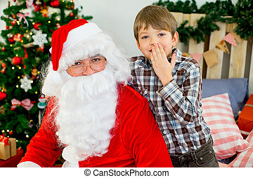 Santa Claus and cute boy getting ready for Christmas