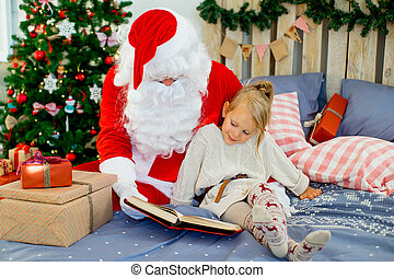 Santa Claus and cute girl getting ready for Christmas