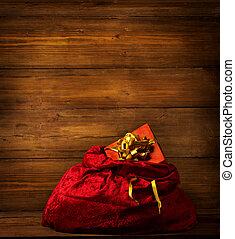 Santa Claus Bag, Christmas Red Sackful on Brown Wooden Bacground, Full Xmas Present Gift