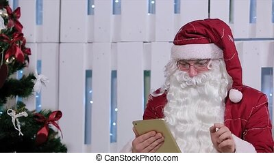 Santa Claus Buy and Pay on Digital Tablet in Room with Christmas Tree and Gifts