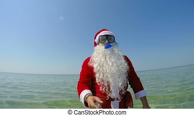 Santa Claus diver on beach vacation coming out of the water