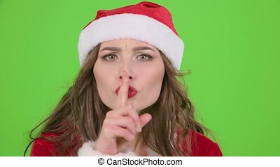 Santa claus girl in red suit points her finger a little more quietly. Green screen. Close up