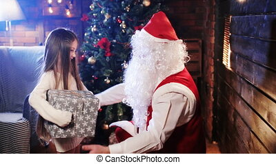 Santa Claus gives a gift to a little girl
