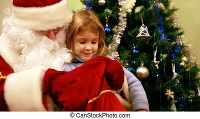 Santa Claus gives gifts to girl near Christmas tree