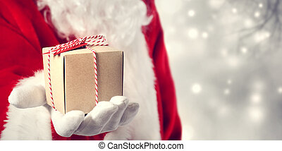 Santa Claus giving a gift - Santa Claus holding a gift in...
