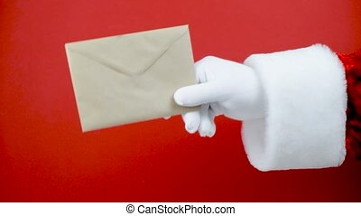 Santa Claus hand hold craft envelope with letter, sending post card. Christmas mail. Wish list.