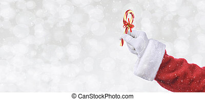 Santa Claus hand holding a candy cane over a silver bokeh background with snow effect