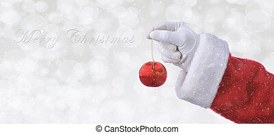 Santa Claus hand holding a red tree ornament over a silver bokeh background with snow effect