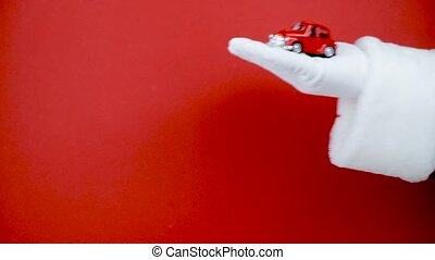 Santa Claus hand holding small red toy car.