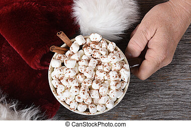 Santa Claus hand with a mug of hot chocolate next ot his hat