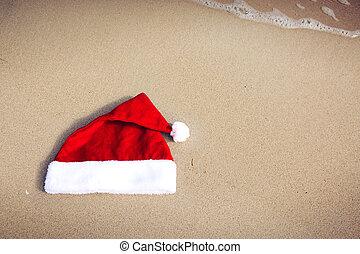 Santa Claus hat on caribbean beach. Christmas background