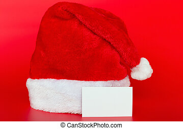 Santa Claus hat on red background with a blank card