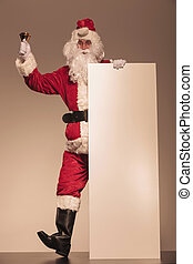 Santa Claus holding a bell and a blank billboard