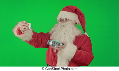 Santa Claus holding a big present  doing a selfie on smartphone on a Green Screen Chrome Key