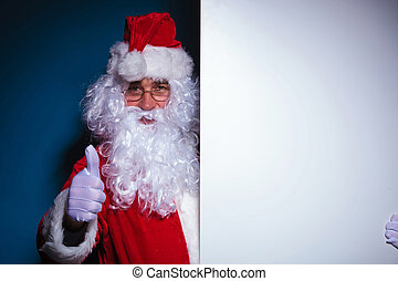 Santa Claus holding a blank board to his left
