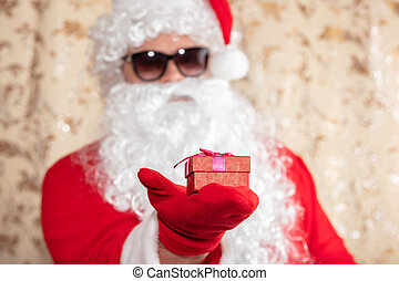Santa Claus holding a Christmas present, a red box with a ribbon. Santa wearing sunglasses, with a long white beard, and is out of focus. Golden blurred sparkling background
