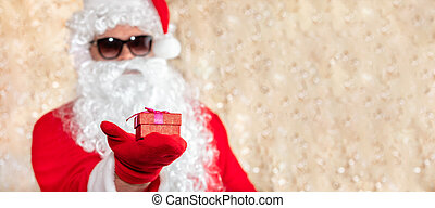 Santa Claus holding a Christmas present, red box with ribbon. Santa wearing sunglasses, with a long white beard, and is out of focus. Golden blurred sparkling background with copy space. Banner size