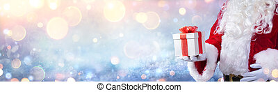 Santa Claus Holding A Christmas Present With Snowy Background And Golden Lights