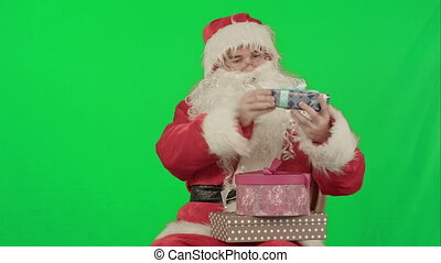 Santa Claus holding a gift in his hand on a Green Screen Chrome Key