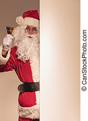 Santa Claus holding a golden bell in his hand