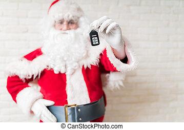 Santa Claus holding car key as Christmas gift at home