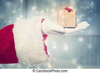 Santa claus holidng a small christmas present - Santa Claus...
