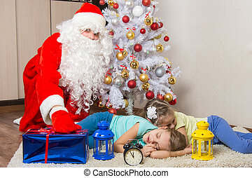 Santa Claus in New Years Eve puts the gift in front of...