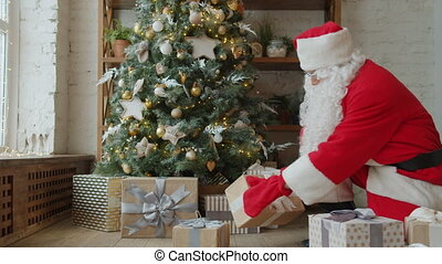 Santa Claus in traditional outfit is putting gifts under Christmas tree on holiday at home, room is beautifully decorated. Occasions and presents concept.