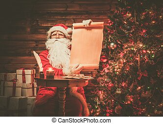 Santa Claus in wooden home interior holding blank wish list...