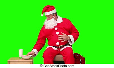 Santa Claus is hungry against a green screen