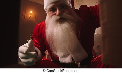 Santa-Claus is opening gift at Christmas night, view from box, wonder at new year holidays, tradition celebration and fairy tale concept