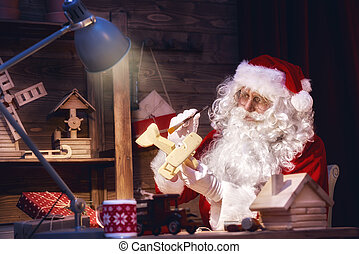 Santa Claus is preparing gifts - Merry Christmas and Happy...