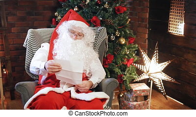 Santa Claus is reading a letter near the Christmas tree