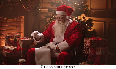 Santa Claus is reading list of good kids and checking gifts for Christmas, sitting in his decorated room at festive evening, fairy tale and wonderful night