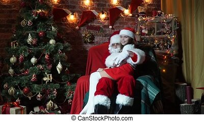 Santa Claus is shakes her the child in his knees
