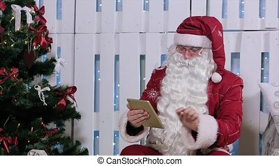 Santa Claus Is Sit and Finger Up to Digital Tablet, Room with Fireplace and Christmas Tree, Gifts.