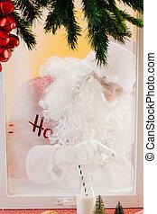 Santa Claus is writing ho-ho-ho on a frozen window on the ...