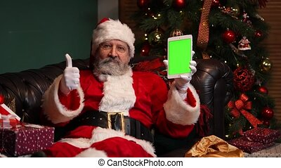 Santa Claus lies on the sofa near a decorated Christmas tree and shows a tablet with a green screen chrome key while making a thumb up gesture. New Years advertising, promotion. E-commerce. Close up. Slow motion.