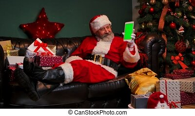 Santa Claus lies on the sofa near decorated Christmas tree and gift boxes, shows tablet with a green screen chrome key, making thumb up gesture. New Years advertising, promotion. E-commerce. Slow motion.