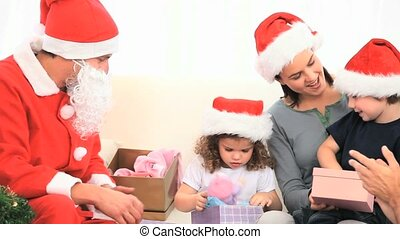 Santa Claus looking at children with their gifts